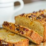 Sliced Mango Ginger Breakfast Bread on cutting board with knife and coffee mug in background