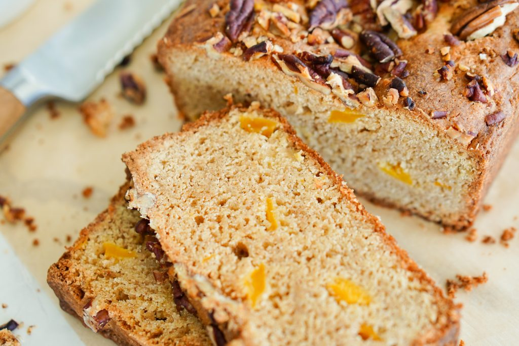 Sliced Mango Ginger Breakfast Bread so you can see the mangoes in the crumb on cutting board
