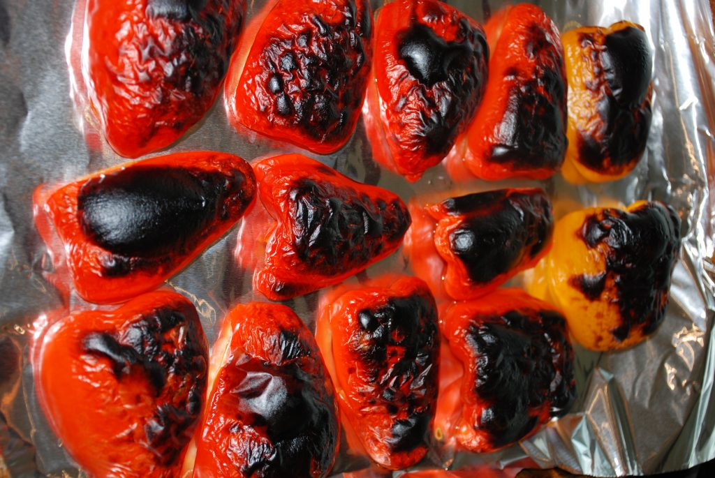 Red bell peppers on a baking sheet after roasting