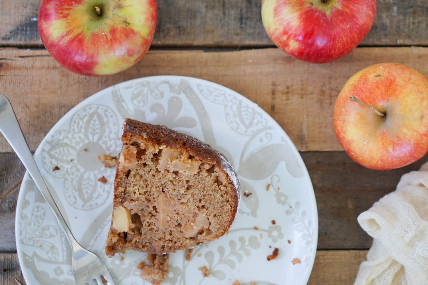 Top down of apple cake with apples in background