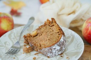Side view close up of apple cake with fork plate and apples in background