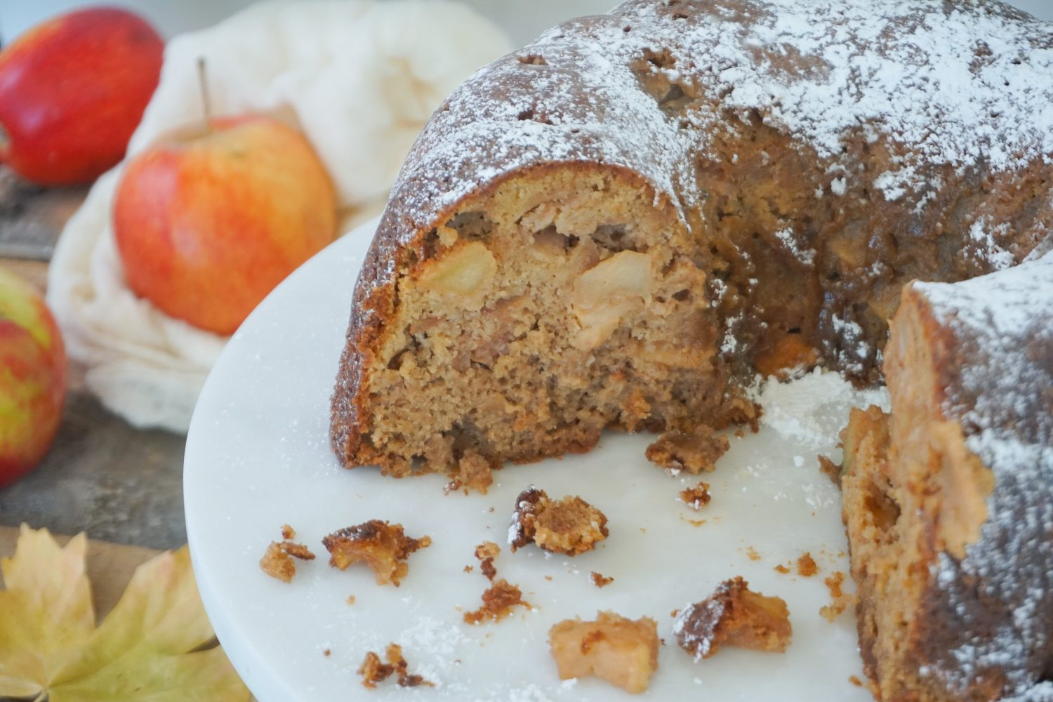 Apple cake showing moist interior with apples in background