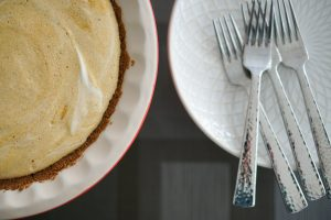 Frozen pumpkin pie in pie plate with plates and forks