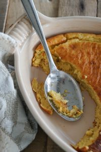 Top down of spoon bread missing from serving dish with messy spoon