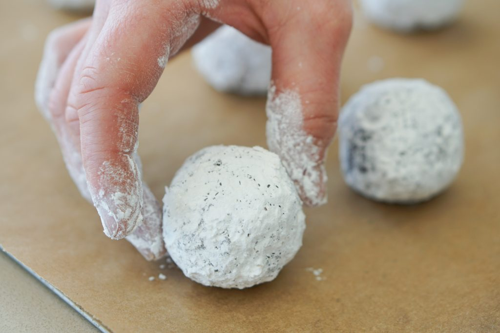 Putting powder sugared dough ball on parchment paper
