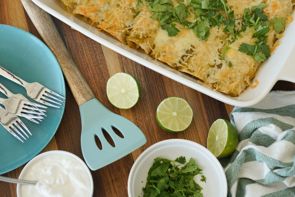 Enchiladas in baking dish with spatula limes and sour cream