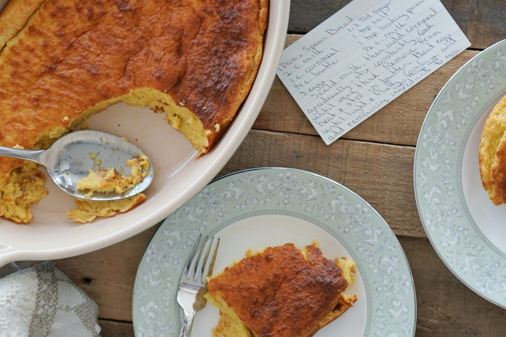 Top down of spoon bread in serving dish with pieces missing and plated with handwritten recipe note card in background