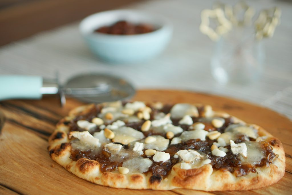 Onion jam and goat cheese flatbread on a wooden cutting board with Key Lime Lexi pizza cutter