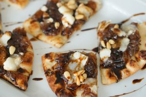 Close up of onion jam and goat cheese flatbread on a white platter