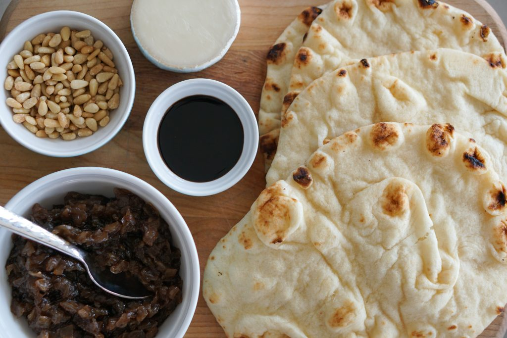 Naan Onion Jam Pine Nuts and Goat Cheese on wooden cutting board