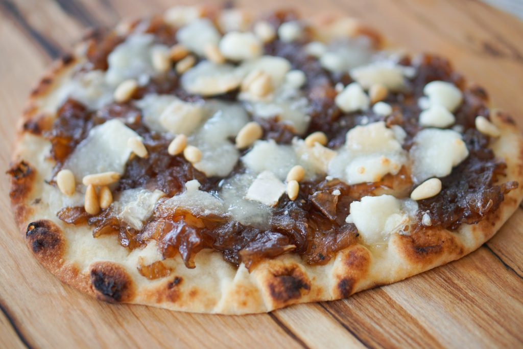 Close up of onion jam and goat cheese flatbread before slicing