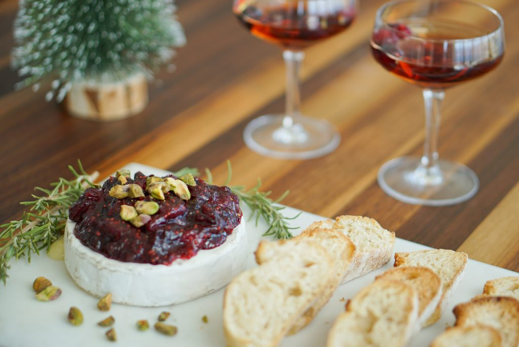 Baked Brie on serving platter with toasts and glasses