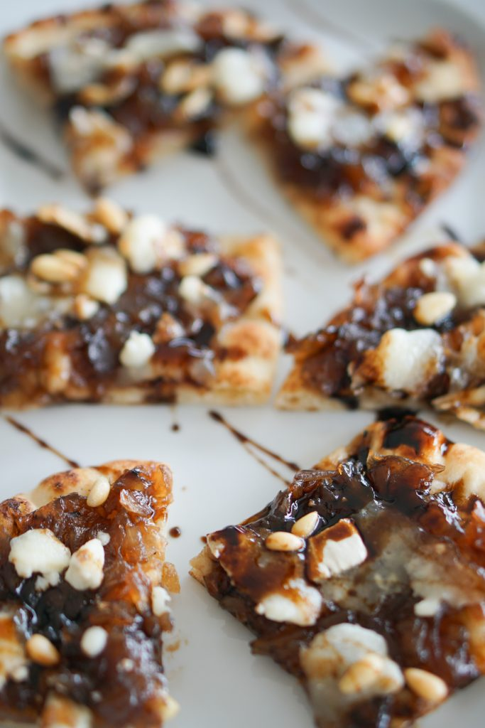 Onion jam and goat cheese flatbread on a white serving platter drizzled with balsamic