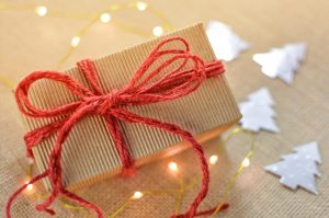 Gift wrapped in brown paper with red bow and christmas tree cut outs in background