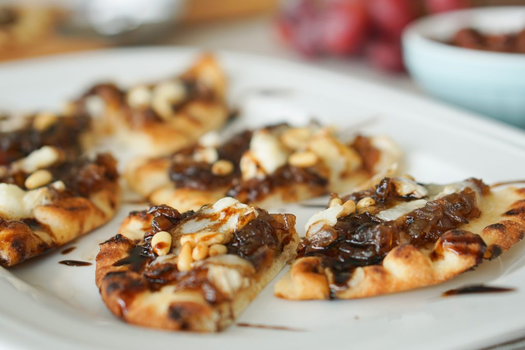 Onion jam and goat cheese flatbread on a platter at a party