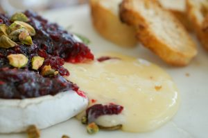 Baked brie with orange cranberry sauce oozing on serving plate toward toasts