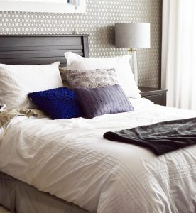 Bed with throw pillows and white comforter