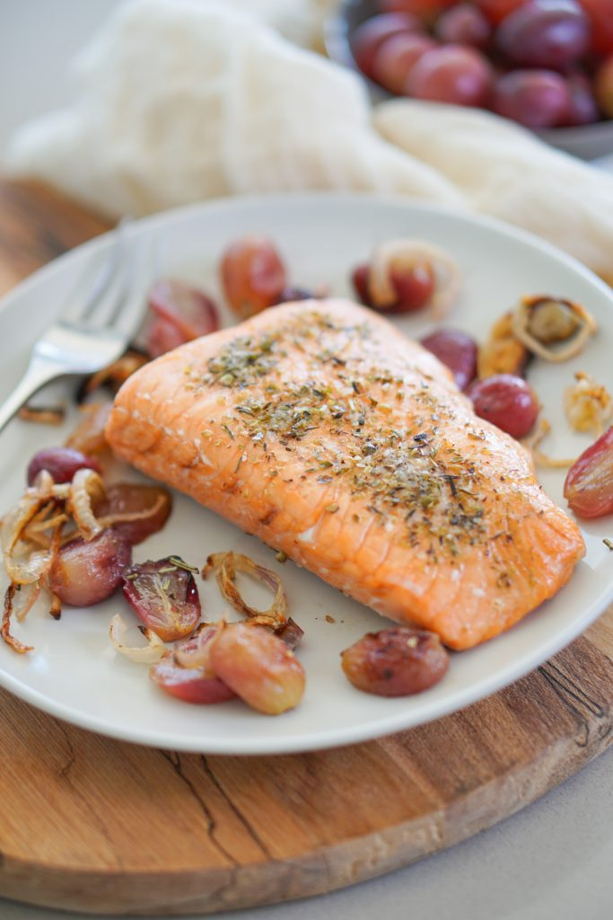 Roasted salmon on plate with roasted grapes shallots and fork