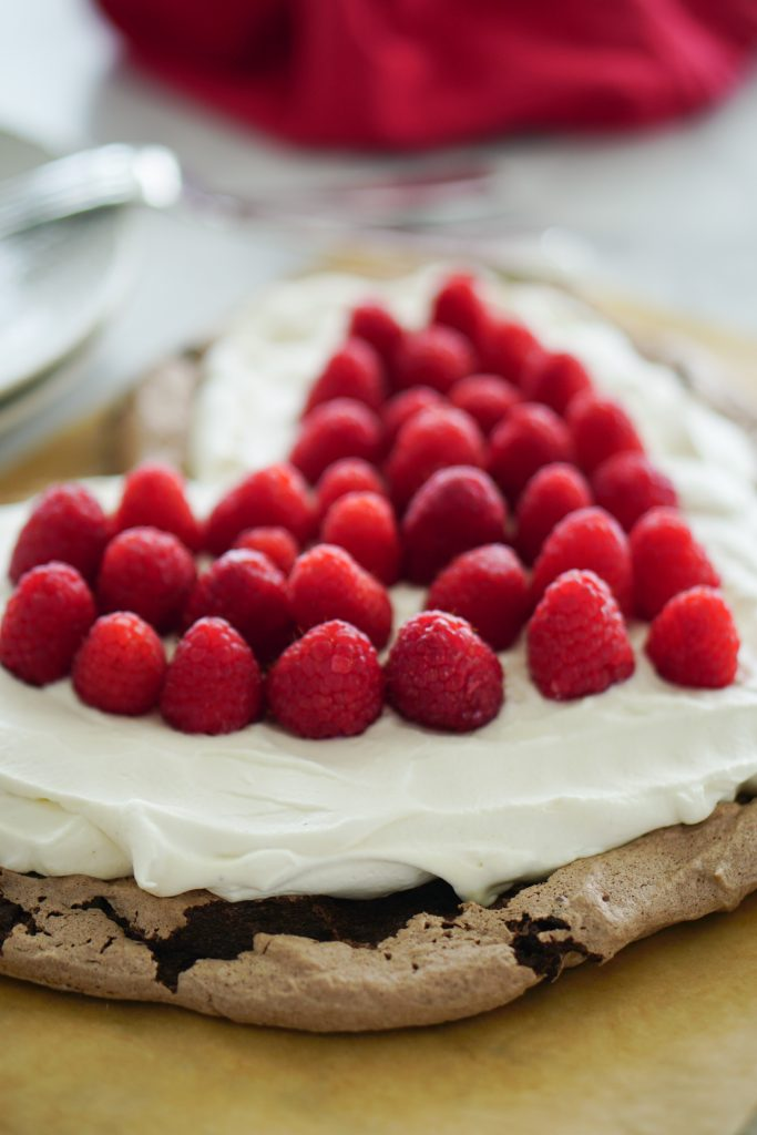 Heart-shaped chocolate Pavlova topped with whip cream and raspberries