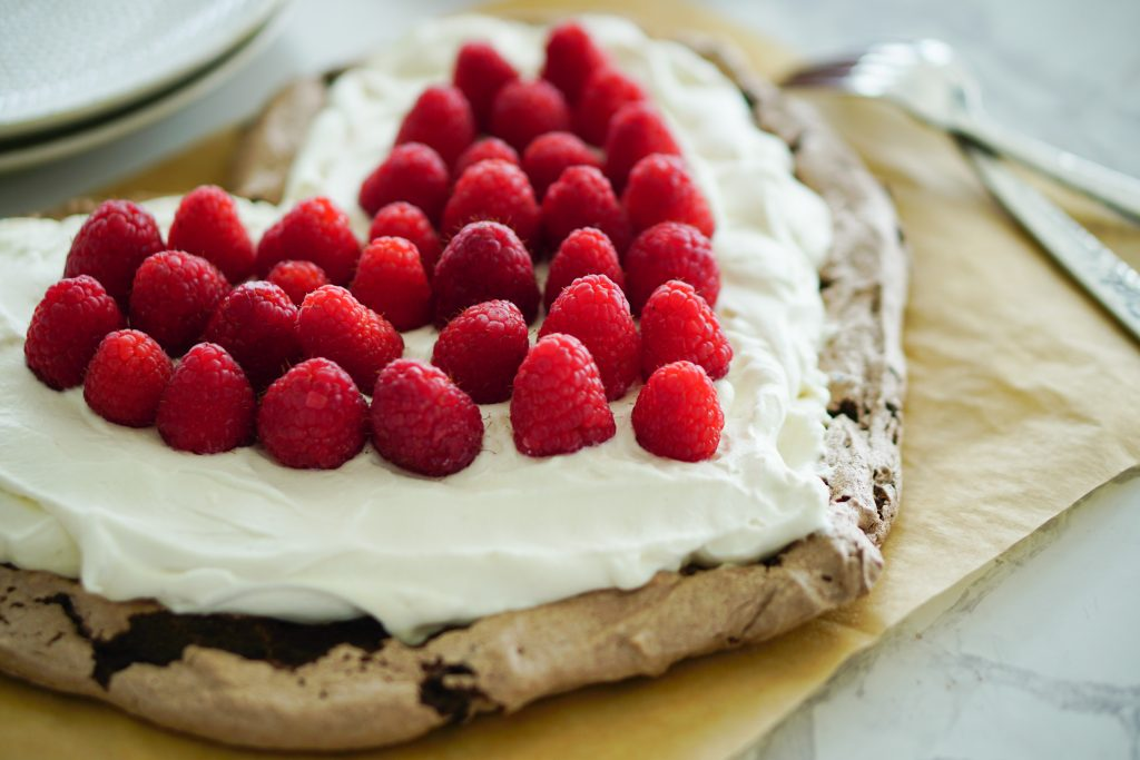 Chocolate pavlova on parchment topped with whipped cream and raspberries