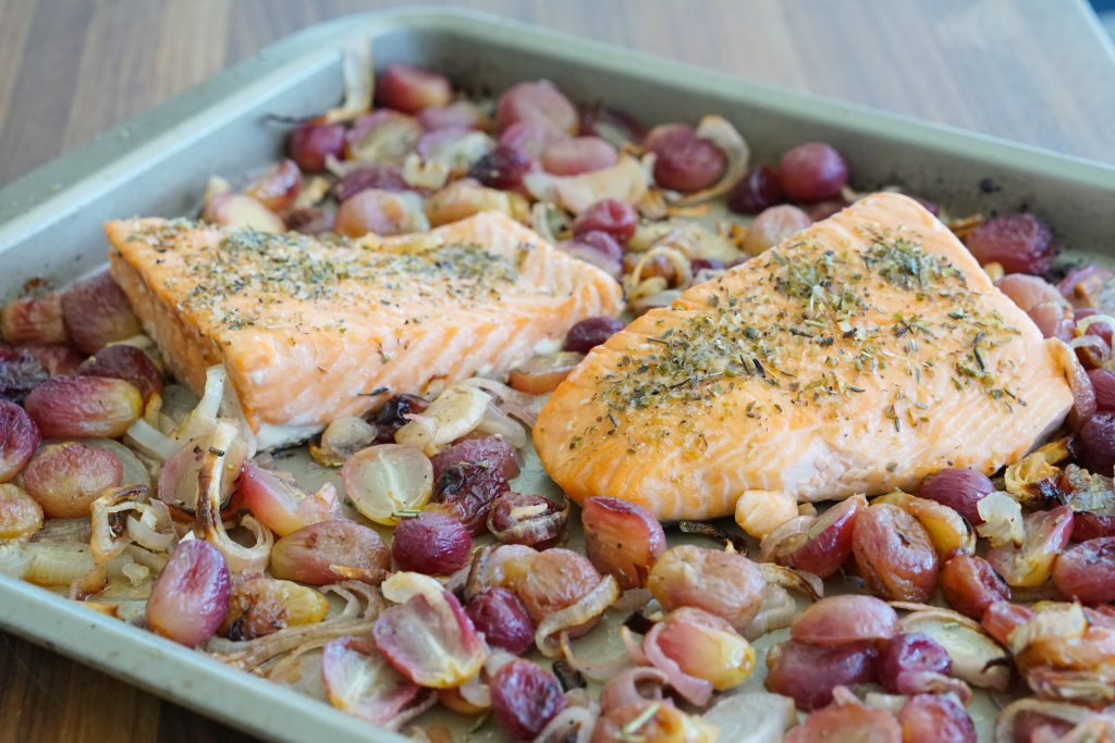 Sheet pan salmon with roasted grapes and shallots on sheet pan prior to plating