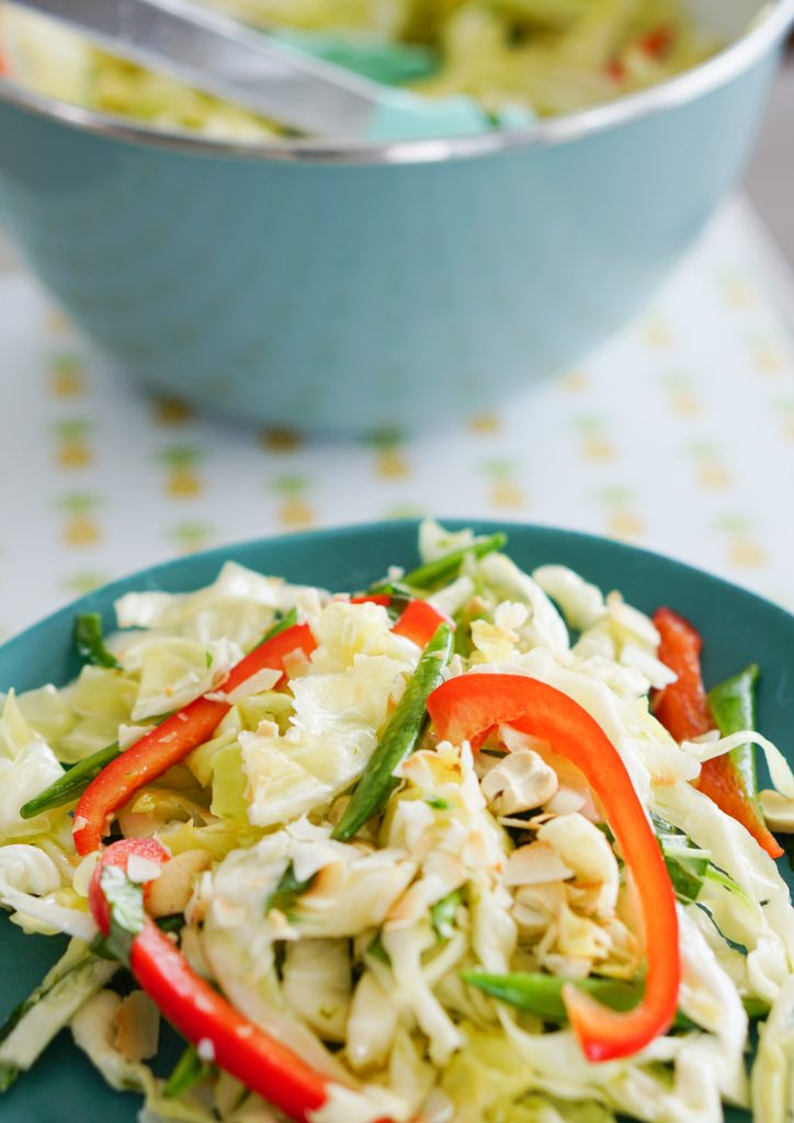 Tropical Slaw on blue plate in foreground with serving bowl and tongs in background
