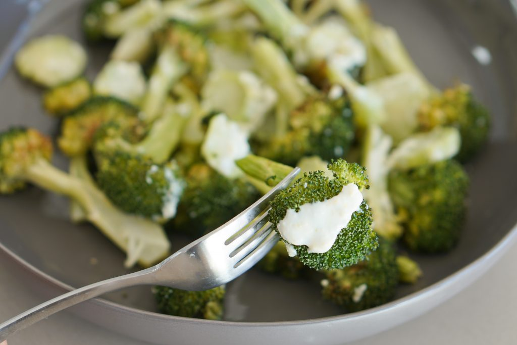 Broccoli in a gray bowl with a fork stabbing a broccoli spear and drizzled with garlic sauce