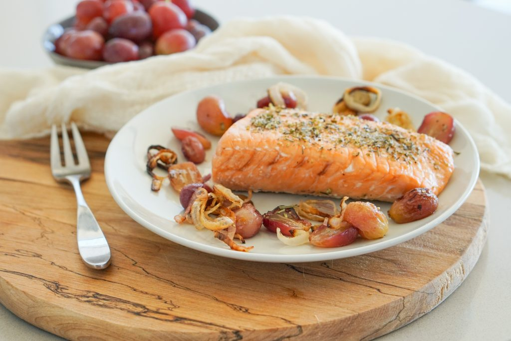 Roasted salmon on a plate with grapes in the background