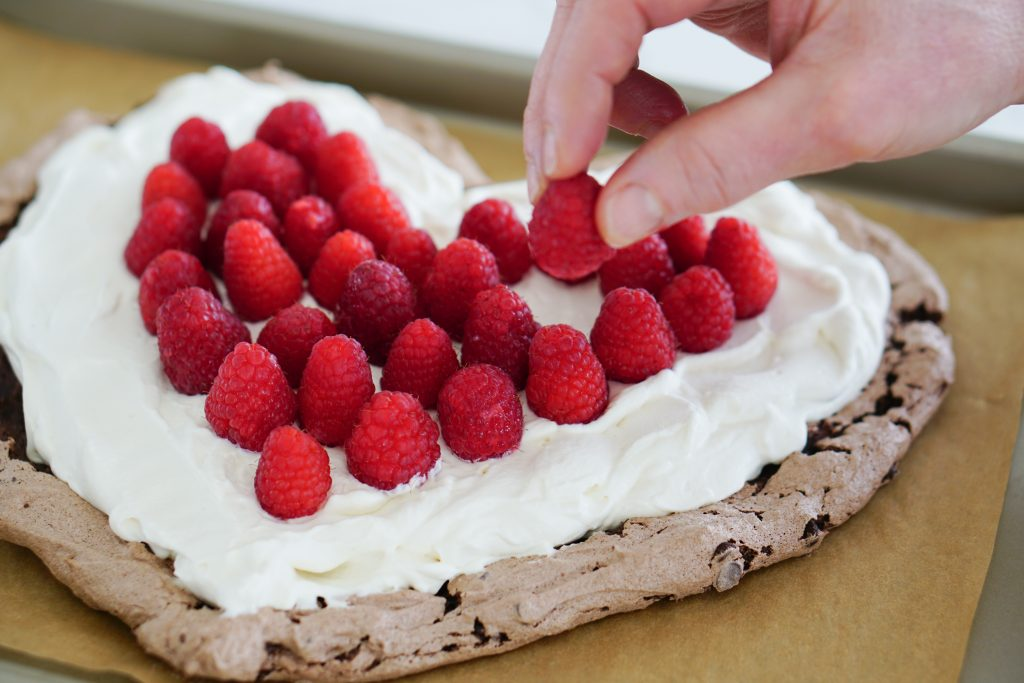 Heart-shaped pavlova with hand adding raspberries to top