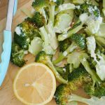 Roasted broccoli topped with lemon garlic sauce on a cutting board with a half lemon and key lime lexi tongs