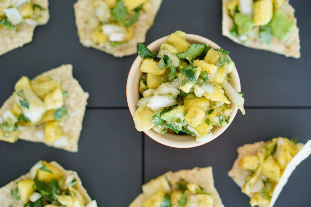 Flat lay with bowl of pineapple salsa surrounded by topped tortilla chips on slate background