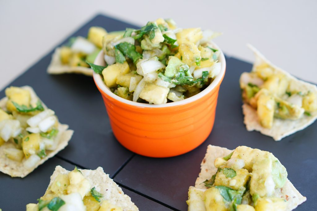 Pineapple salsa in orange cup on slate background surrounded by topped tortilla chips
