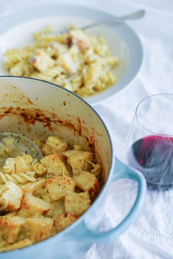 French onion pasta bake in blue baking pot with plated bowl and wine glass in background