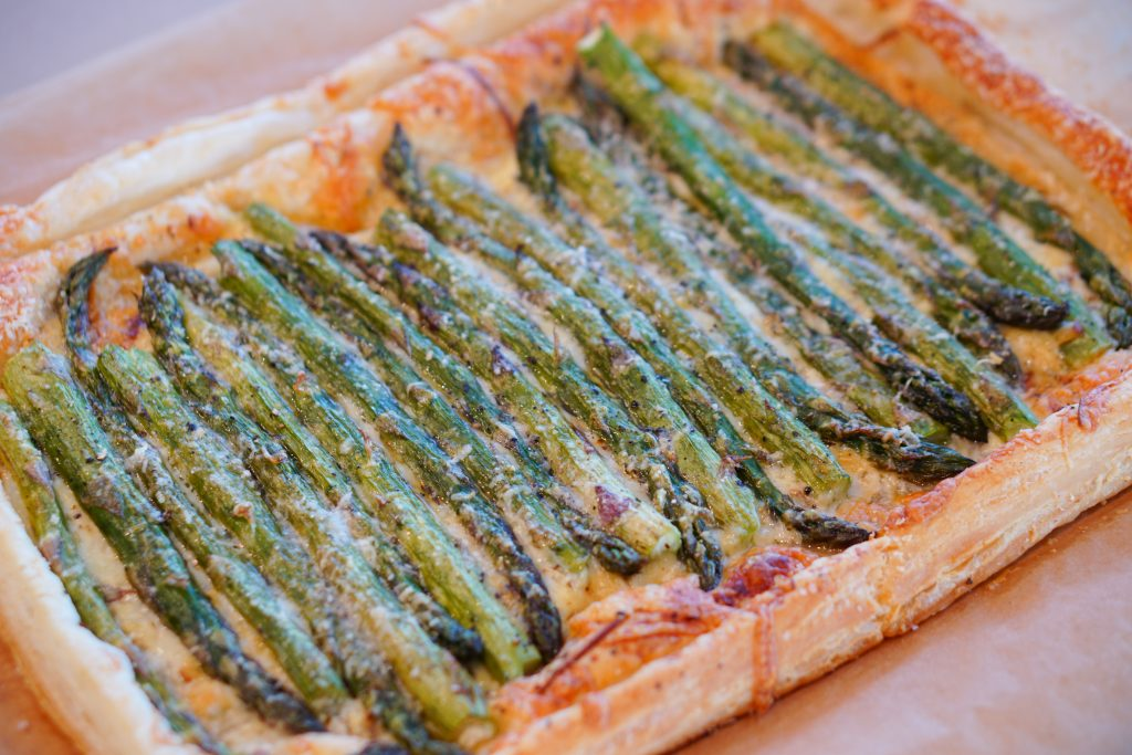 Asparagus and Gruyere Tart on wooden cutting board