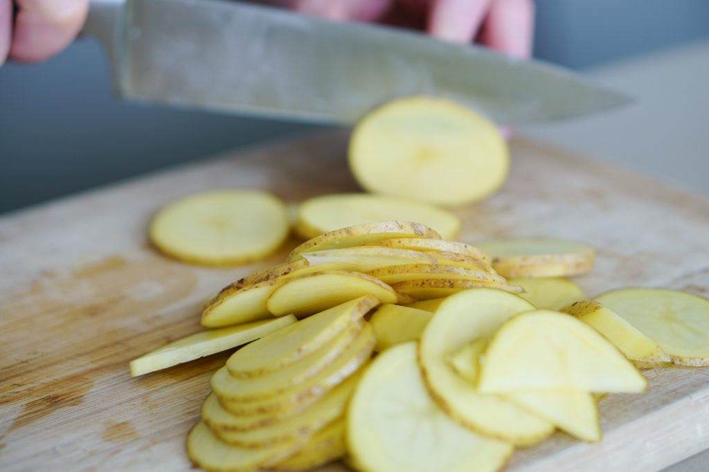 Sliced potatoes on cutting board