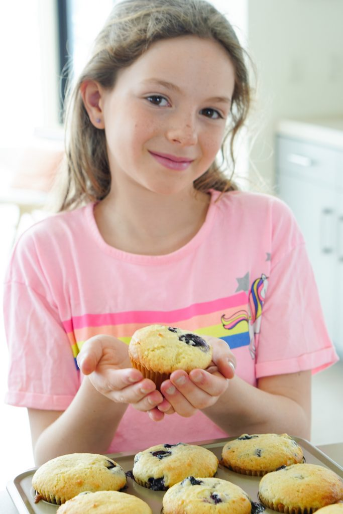 Daughter holding blueberry muffin