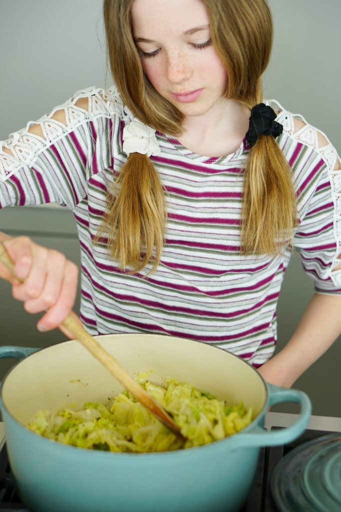 Daughter stirring cabbage