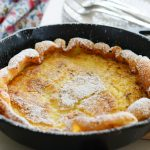 Dutch baby with plates forks napkin in background