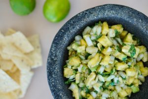 Pineapple Avocado Salsa with Cilantro in molcajete with limes and chips in background
