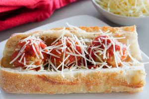 Turkey meatball sub sandwich topped with sauce and cheese plated with napkin in background