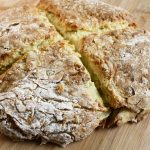 Top lay irish soda bread on wooden cutting board