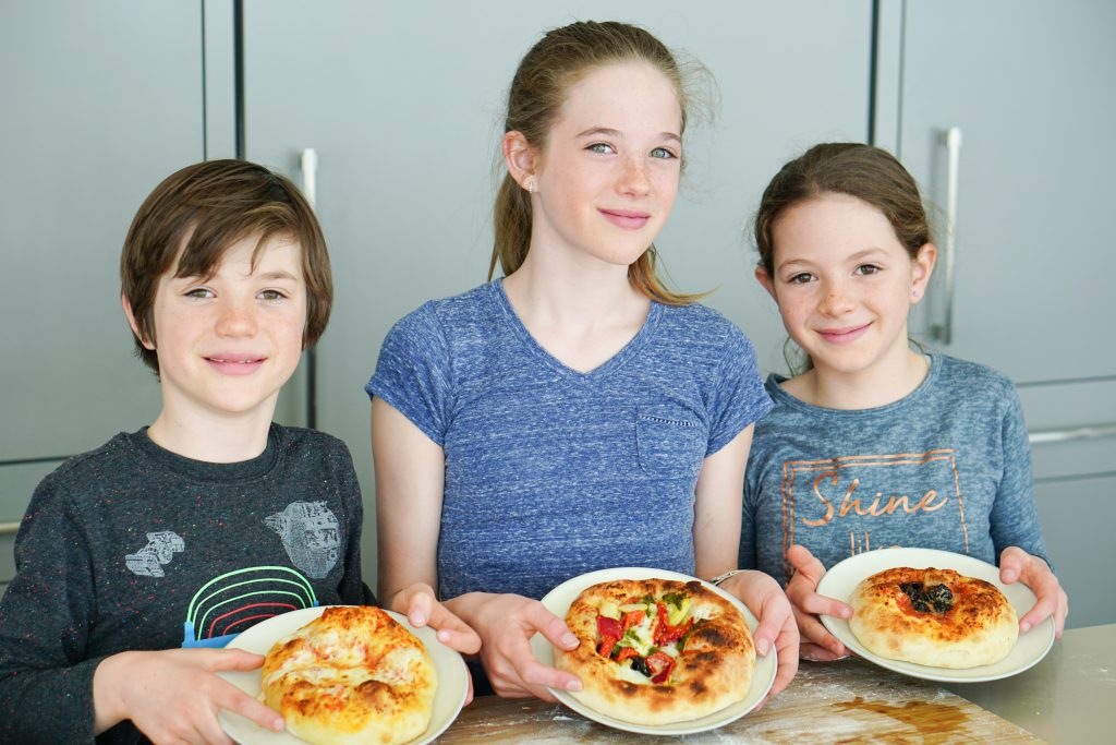 Kids holding plates showing their make your own pizzas