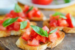 Bruschetta in the foreground with a tomato on a plate in the background