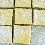 Key Lime Bars with Chocolate Crust on counter with dusted powder sugar
