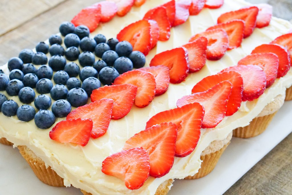 Side angle of Pull-Apart cupcakes topped with blueberries and strawberries in US flag design so you can see individual cupcakes