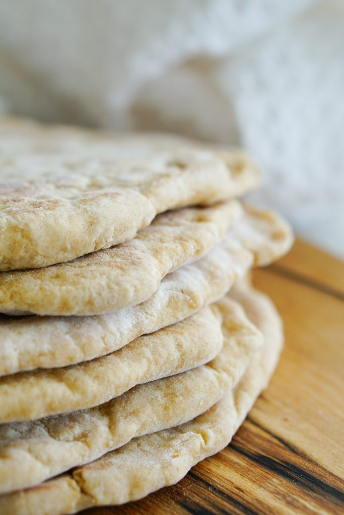 Flatbreads stacked on board with kitchen towel in background