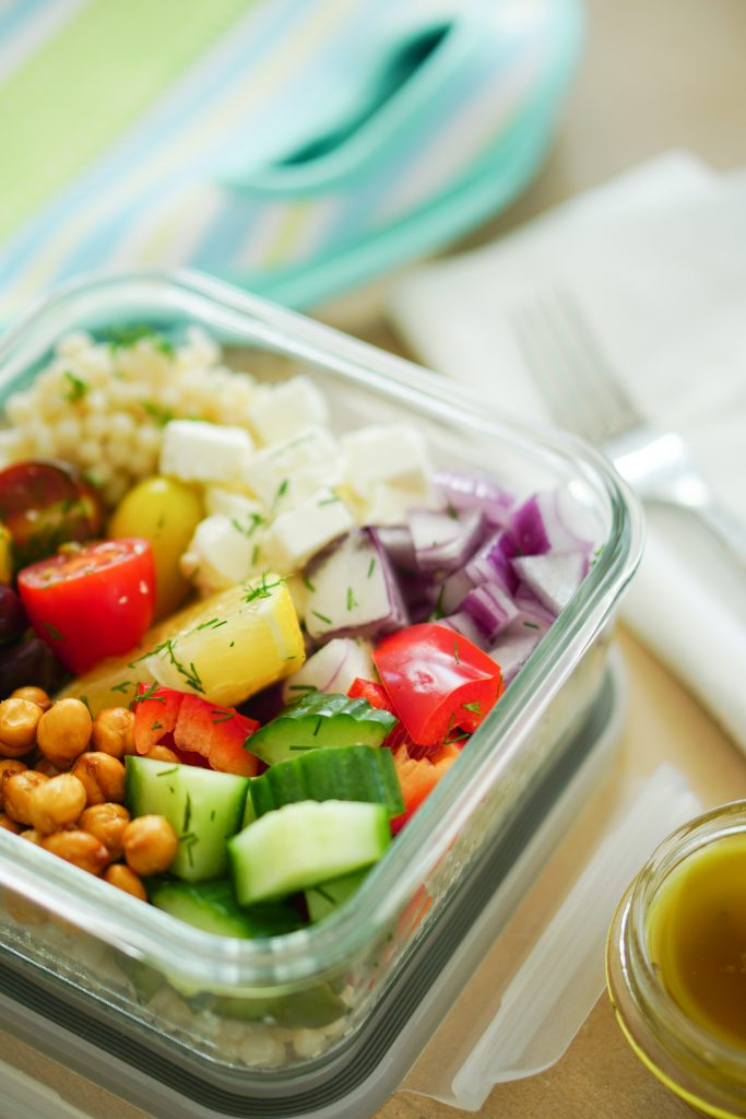 Greek-Style Couscous Salad in a to-go container with lunch tote in background
