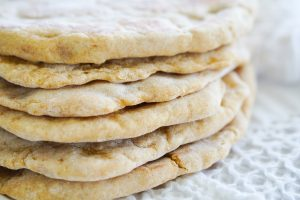 Flatbreads stacked on tea towel