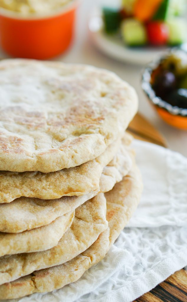 Flatbreads stacked on white tea towel with olives in background