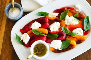 Roasted Bell Pepper Caprese Salad on a serving platter with olive oil and spice blend and salt